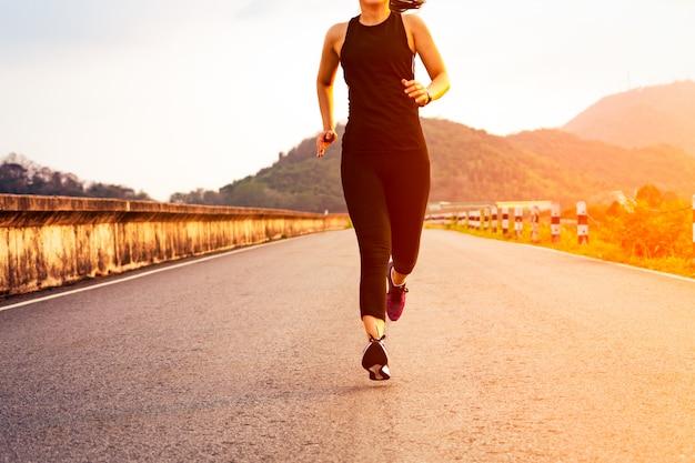 Спорт женщина работает на дороге. фитнес женщина тренировки на закате