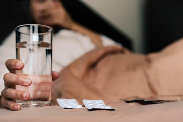 病気の女性の手を持つ薬はコップ一杯の水を保持する、ヘルスケアおよび薬の回復