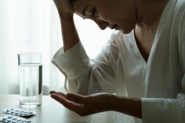 頭痛の女性の手は水のガラスと薬を保持します。
