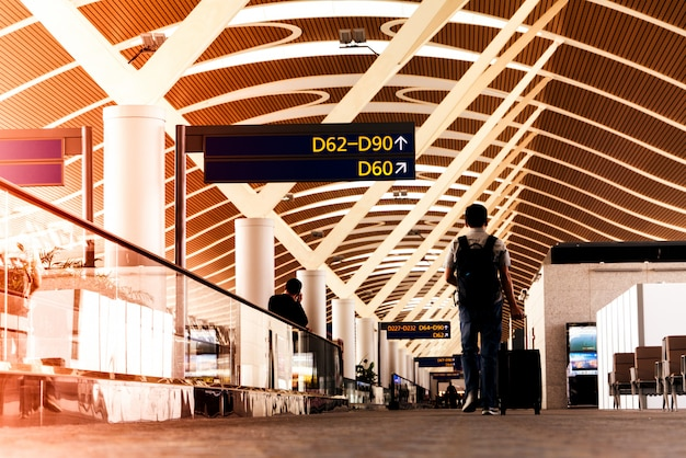 空の旅のために空港ターミナルの通路を歩く旅行か旅行かばんを持って旅行者