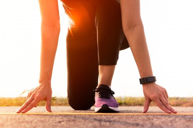 準備完了開始位置に走っている女性と長い道のりを走るつもり