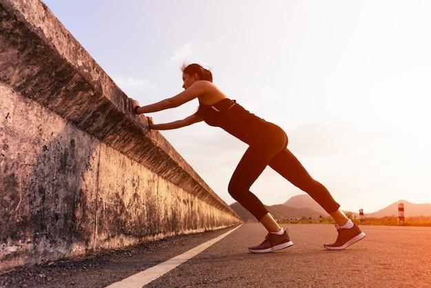 スポーツ女性ランナーの長い道を走る前に筋肉を伸ばす