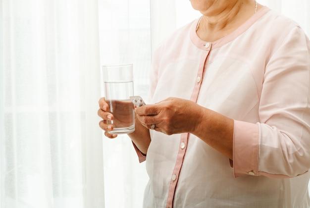 年配の女性は一杯の水で薬を飲む、ヘルスケアおよび薬の回復の概念