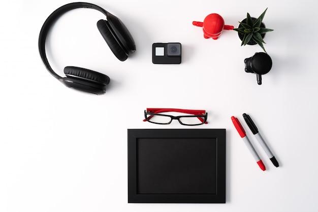 Макет, фоторамка, экшн-камера, наушники, очки, ручка и кактус, красный и черный объект на белом фоне