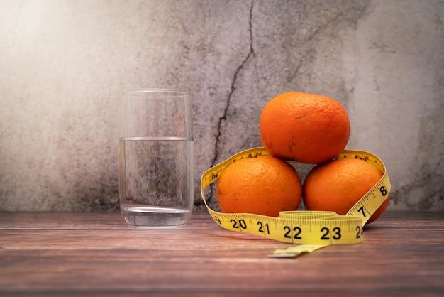 測定テープと木製のテーブルの上の水を飲むの食事療法のための新鮮な果物。ダイエットと健康的なライフスタイルのコンセプト