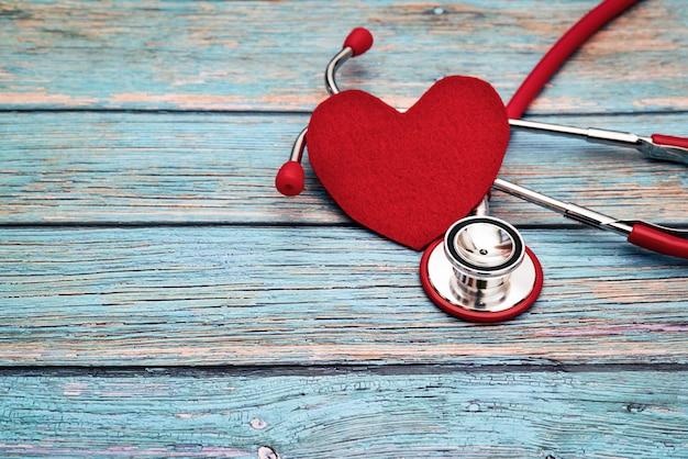世界保健デー、ヘルスケアと医療の概念、赤い聴診器と青い木製の背景に赤いハート