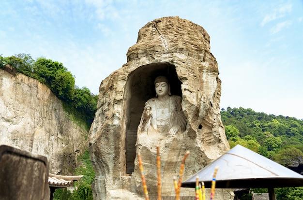 青い空を背景に石の彫刻の仏像