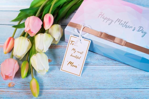 Концепция счастливого дня матери с подарочной коробкой и цветком, бумажной биркой