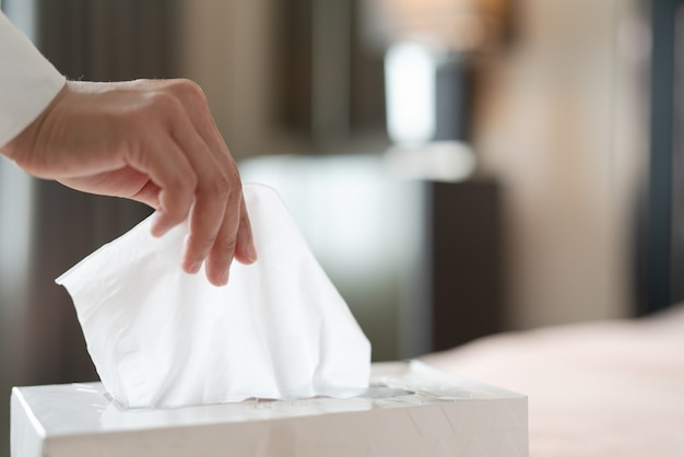 ティッシュボックスからナプキン/ティッシュペーパーを選ぶ女性の手
