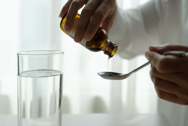 スプーンにボトルから薬や咳止めシロップを注ぐ女性の手。