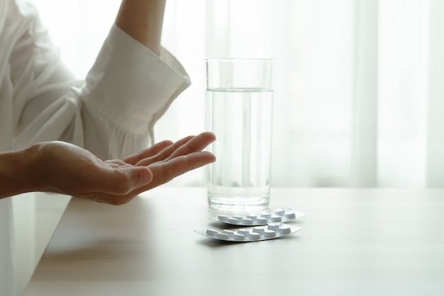 落ち込んでいる女性の手は水のガラスと薬を保持します。