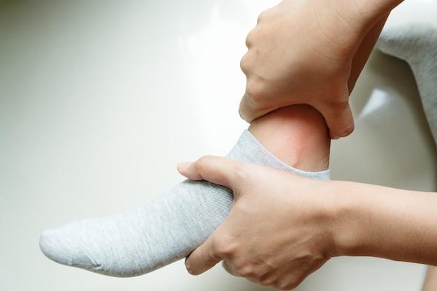 女性が痛みの足首の足に触れる