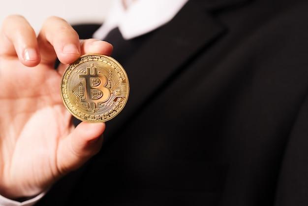 女性は暗号通貨コインを手に持っている。