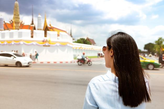 バンコク、タイで日没で壮大な宮殿とワットプラケオに旅行する若い女性