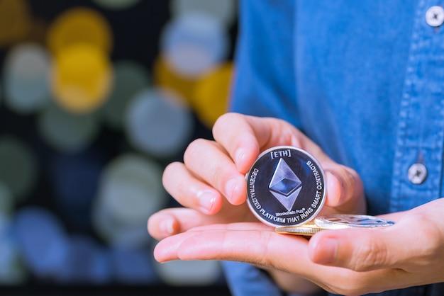 暗号通貨コイン-イーサリアム。女性は暗号通貨コインを手に持っています