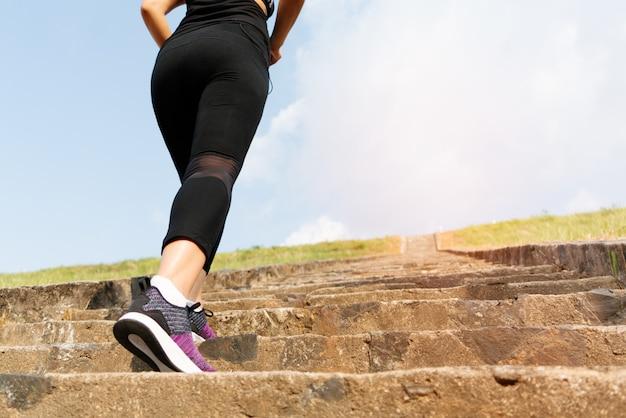 スポーツの女性がトレーニングのための石のステップにステップアップ