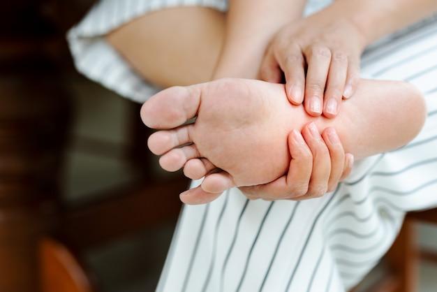 彼女の痛みを伴う裸足をマッサージする女性