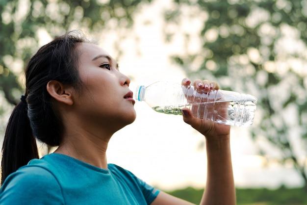 Фитнес азия женщина питьевая вода после бега