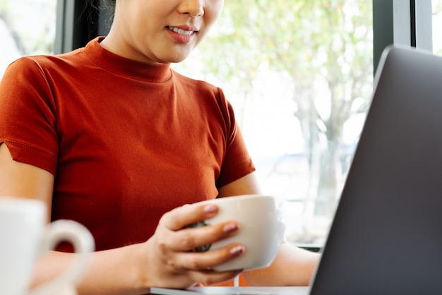 アジアの女性は、ノートパソコンのキーボードで入力しながらコーヒーを保持します。コーヒーを飲みながらオフィスで働く女性