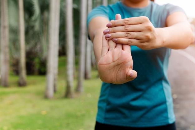 運動する前に前腕を伸ばしてスポーツ女性
