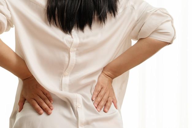 自宅で背中の痛み。女性は腰痛に苦しんでいます。ヘルスケアおよび医療の概念