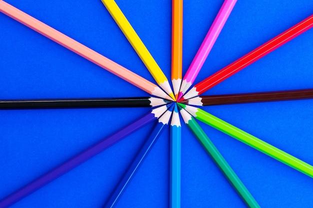 青い背景に様々な色鉛筆