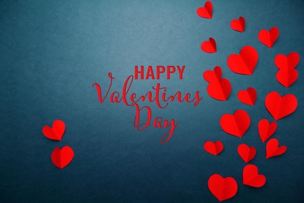 青色の背景、抽象的なフラットレイアウト、トップビューに赤いハートのバレンタインカード