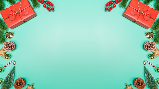Рождественский фон концепции. вид сверху рождественские украшения, санта-клаус и олени с красной подарочной коробке на зеленом фоне