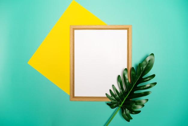 Летняя композиция. тропические пальмовые листья, желтый бумажный бланк, рамка для фотографий на пастельных зеленом фоне.