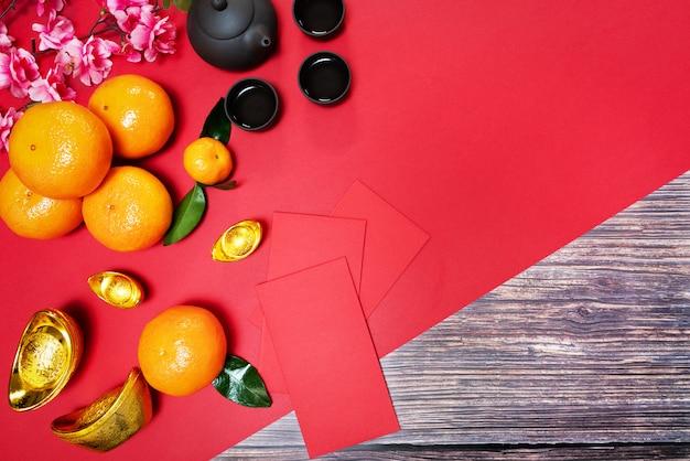 Китайский новый год с красным конвертом в оранжевом и китайском чайнике. перевод текста на картинке: процветание, богатство и здоровье