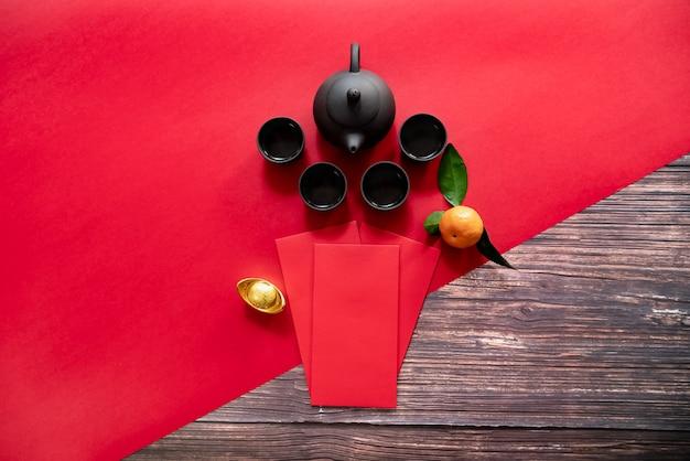 Китайский новый год с красным конвертом и китайским чайником. перевод текста на картинке: процветание, богатство и здоровье