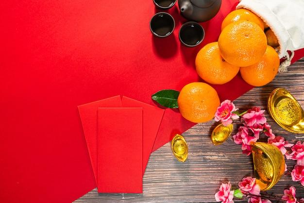 Китайский новый год предлагает красный конверт китайский чайник и апельсин