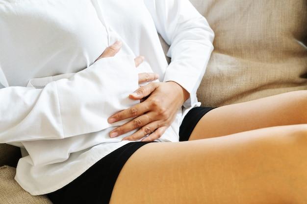 Молодая женщина, страдающая боли в животе, сидя на диване и чувствуя боль в животе