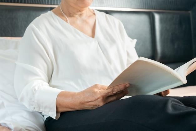 Занятия для пожилой женщины читают книгу и остаются дома, чтобы избежать риска