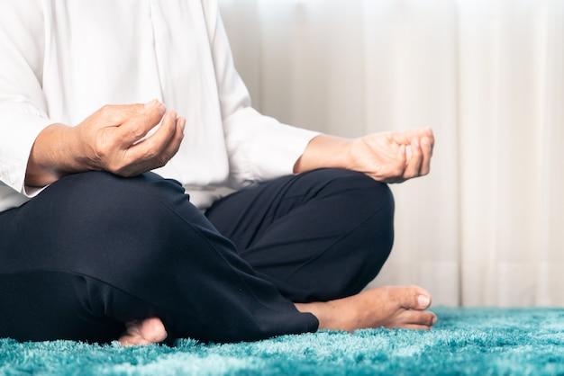 Карантинная активность для пожилой женщины, которая медитирует, оставаясь дома, чтобы избежать риска