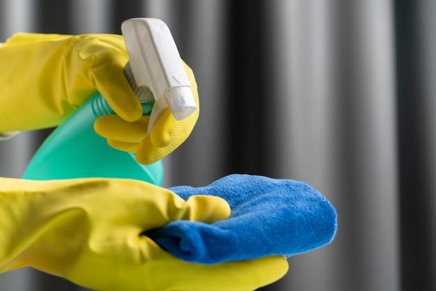 Руки держат чистящий спрей и ткань