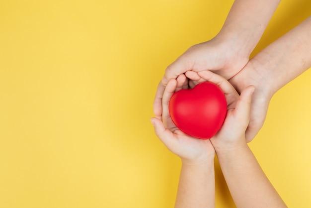 世界保健デー、赤いハート、ヘルスケア、愛と家族の保険の概念を保持している大人と子供の手