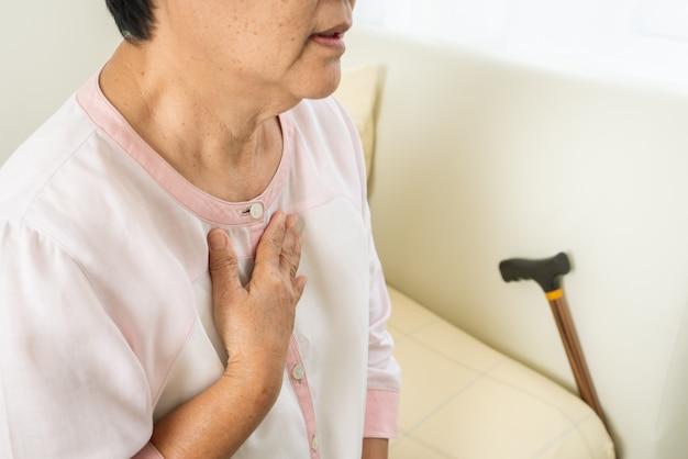 Старушка сердечного приступа держа комод в комнате кровати, проблеме здравоохранения старшей концепции