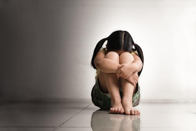 Один и испуганный ребенок плачет в темной комнате