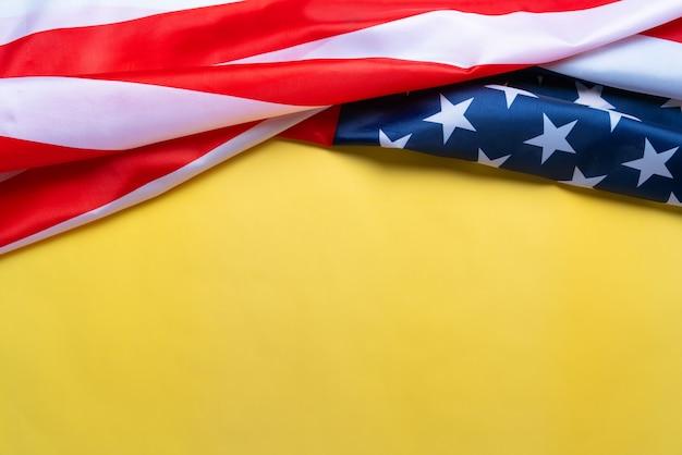 アメリカの記念日と独立記念日のコンセプト、黄色の背景にアメリカ合衆国の国旗
