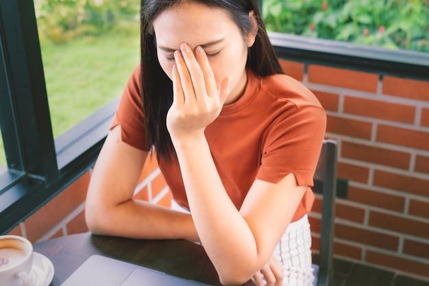 Усиленная головная боль коммерсантки работая на портативном компьютере. негативные эмоции человека выражение лица чувства