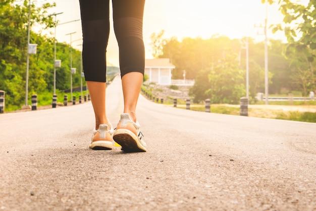 Спортивные женские ноги бегуна готовы к бегу по лесной тропе