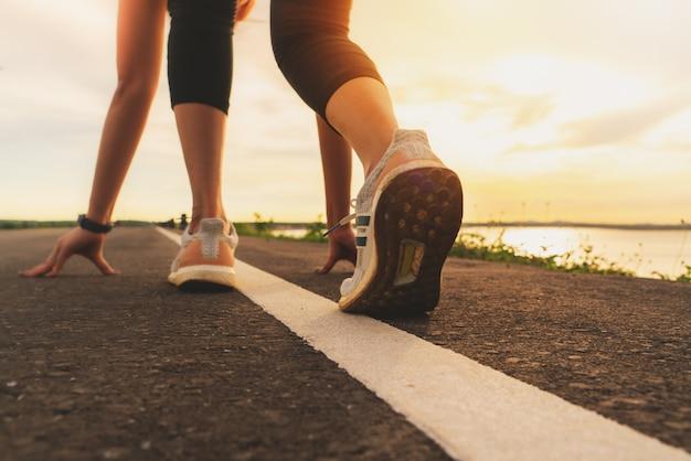 靴の日没の湖のクローズアップで実行されているスポーツランナーの足