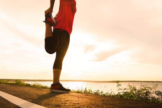 Женщина растягивает мышцы ног, готовится к закату тропа