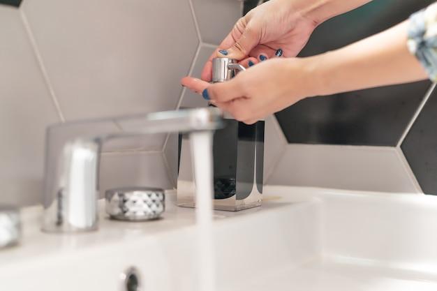 トイレで液体石鹸で手を洗う女性