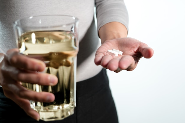 水の薬の回復のコンセプトのガラスと薬を持って女性の手