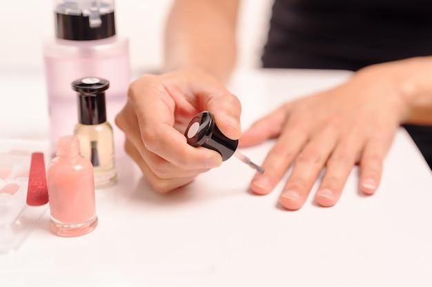 マニキュアとマニュファクチュールのボトルでマニキュアを塗っている女性のファッションと美しさ