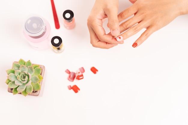 女性のマニキュアとゲルで爪の形を取り付けるファッションと美容のコンセプト