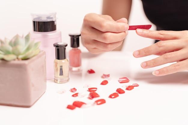 女性のマニキュアと家庭でゲルと爪の形を取り付けるファッションと美容のコンセプト