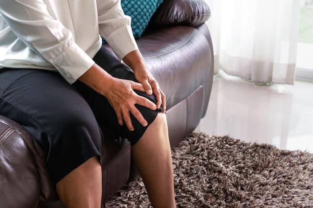 Старая женщина, страдающая от боли в колене дома, концепция проблемы со здоровьем